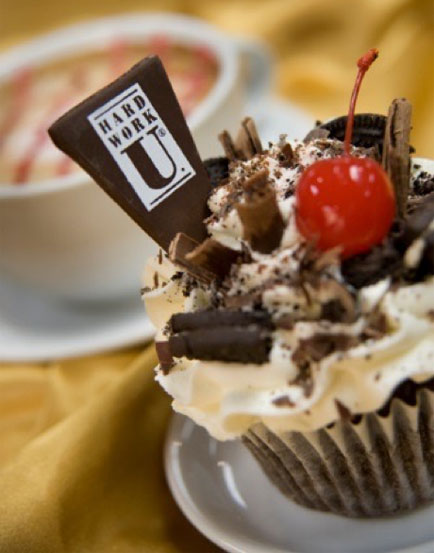 Chocolate cupcake with white frosting, a cherry and the 'Hard Work U' logo on a chip of chocolate