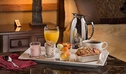 A breakfast platter with orange juice, coffee, fresh fruit, parifats and a loaf of specialty bread