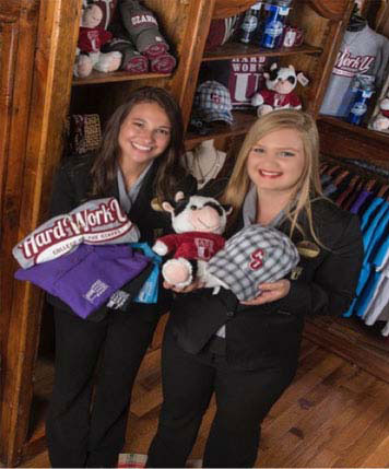 Two female student workers standing in the Keeter Center gift shop