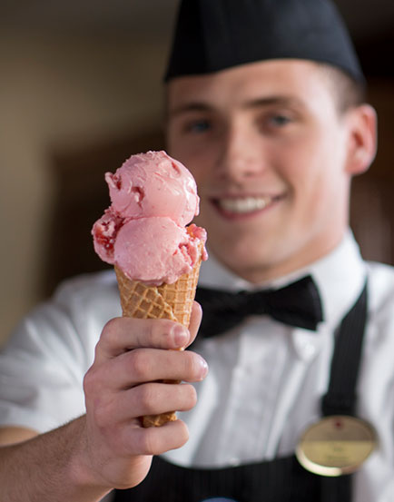 Smiling student worker holding a sugar cone with pink ice cream