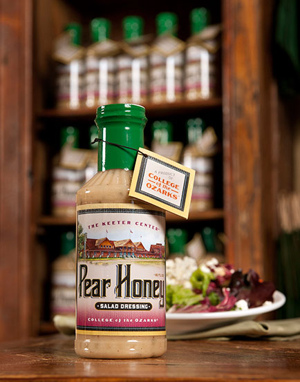 Bottle of Pear Honey salad dressing in front of a salad