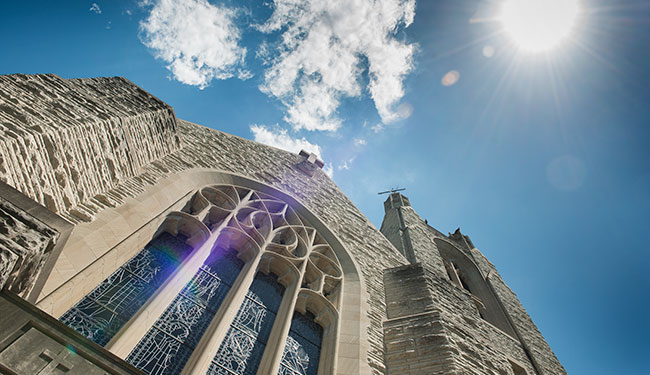 A skyward view of the front of the Williams Memorial Chapel with the sun in the upper right corner to encourage