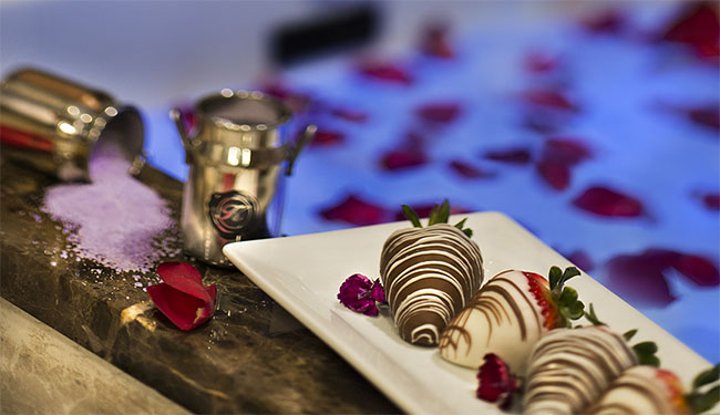 Decorated strawberries on a plate that is sitting on the side of a whirlpool tub filed with water and rose pedals.