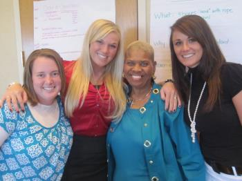 Four women at the S. Truett Cathy Poverty Summit pose with each other and smile